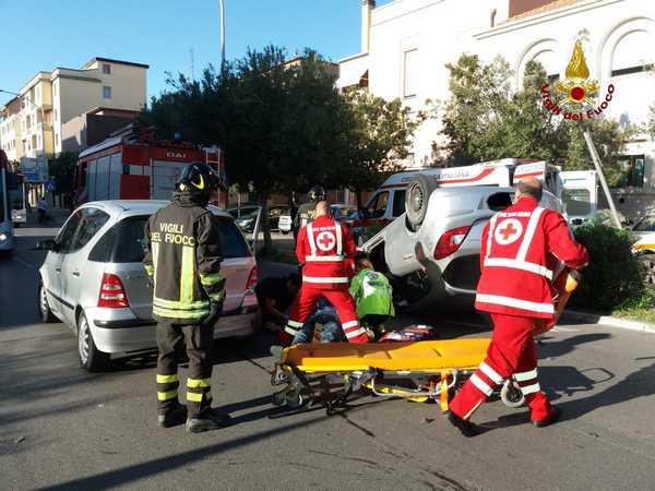 Incidente in città: scontro tra due auto, una macchina si ribalta in mezzo alla strada